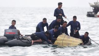 In this Jan. 10, 2021, file photo, Indonesian Navy divers pull out a part of an airplane out of the water during a search operation for the Sriwijaya Air passenger jet that crashed into the sea near Jakarta, Indonesia.