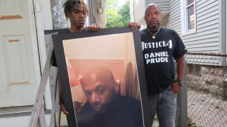 """FILE - In this Sept. 3, 2020, file photo, Joe Prude, brother of Daniel Prude, right, and his son Armin, stand with a picture of Daniel Prude in Rochester, N.Y. Daniel Prude, 41, suffocated after police in Rochester put a """"spit hood"""" over his head while he was being taken into custody. He died March 30, after he was taken off life support, seven days after the encounter with police. The independent investigator leading a probe of the city's handling of Prude's death says the ex-police chief is refusing to cooperate."""