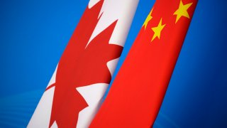 In this Nov. 12, 2018, file photo, flags of Canada and China are placed for the first China-Canada economic and financial strategy dialogue in Beijing, China. China says it has lodged a formal complaint with Canada over T-shirts ordered by one of the country's Beijing Embassy staff that allegedly mocked China's response to the coronavirus outbreak.