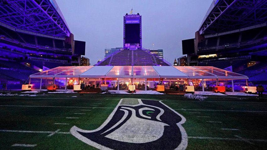 People eat dinner in an outdoor dining tent set up near the logo of the Seattle Seahawks NFL football team