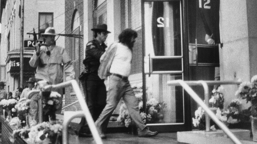 In this Oct. 24, 1981, file photo, David J. Gilbert, right, is escorted by police into the Village Hall in Nyack, N.Y., for a hearing on felony murder charges stemming from the Oct. 20, 1981, Brink's armored car robbery at a mall in Nanuet, N.Y., and a subsequent shootout with Nyack police that left three people dead. Now 76 years old, Gilbert, is still imprisoned in New York state after nearly four decades. Gilbert's son, San Francisco chief District Attorney Chesa Boudin, and other allies are lobbying for clemency for Gilbert as coronavirus cases rise among prison inmates.
