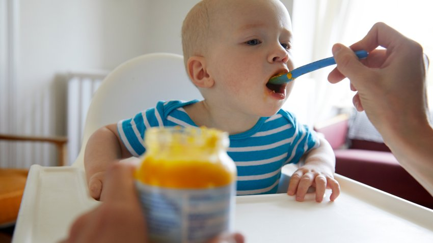Baby taking a bite of food from a spoon with jar of baby food in foreground