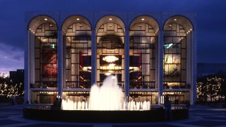 Exterior view of the Metropolitan Opera House at night in New York, New York.