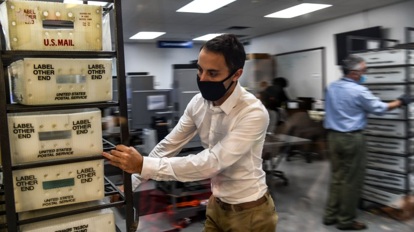 Electoral workers are seen during the vote-by-mail ballot scanning process at the Miami-Dade County Election Department in Miami, Florida on November 3, 2020. -