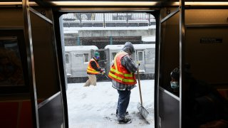 Workers clear snow off a subway station platform in the Midwood neighborhood of Brooklyn