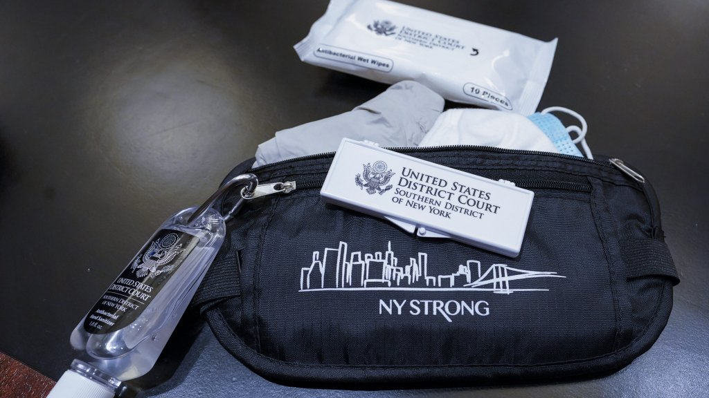 A pouch given to jurors containing face masks, gloves, disinfectant wipes, hand sanitizer and forehead thermometer strips is shown in a courtroom at a Manhattan federal courthouse, Friday, March 12, 2021, in New York.