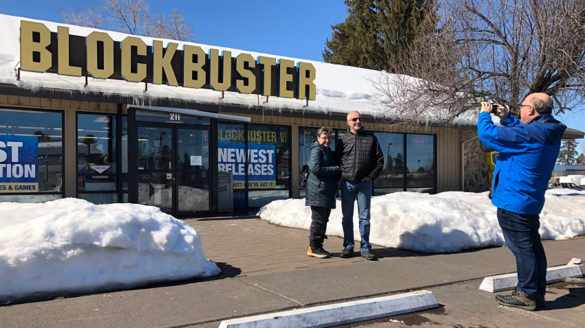FILE - In this March 11, 2019, file photo Debby Saltzman, of Bend, Ore., poses for a photo, in front of the last Blockbuster store with her twin brother, Michael, visiting from Melbourne, Australia, in Bend, Ore. Taking the photo is Saltzman's husband, Jeremy Saltzman. The new Netflix movie called The Last Blockbuster that began airing March 15, 2021 is generating interest in the store, which became the last Blockbuster location on Earth when a location in Perth, Australia shut its doors in 2019.