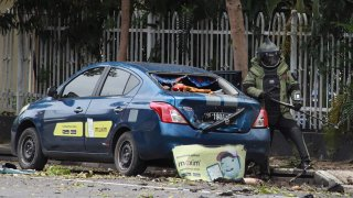 An Indonesian anti-bomb unit (C) collects evidences after a bomb exploded in Makassar on March 28, 2021.