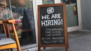 """In this March 5, 2021, file photo, a """"we are hiring sign"""" in front of the Buya restaurant in Miami, Florida. The restaurant is looking to hire more workers as the U.S. unemployment rate drops to 6.2 percent, as many restaurants and bars reopen. Officials credit the job growth to declining new COVID-19 cases and broadening vaccine immunization that has helped more businesses reopen with greater capacity."""