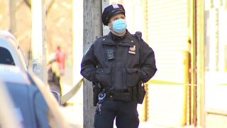 Police officer in New York City stands at the crime scene of a shooting in Brooklyn