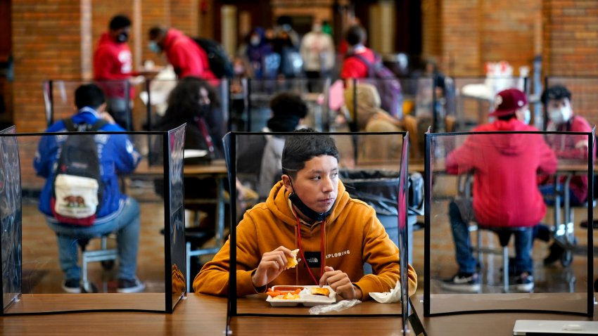 freshman Hugo Bautista eats lunch separated from classmates by plastic dividers at Wyandotte County High School in Kansas City