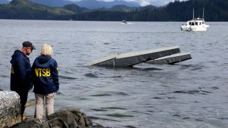 FILE - In this photo provided by the National Transportation Safety Board, NTSB investigator Clint Crookshanks, left, and member Jennifer Homendy stand near the site of some of the wreckage of the DHC-2 Beaver, Wednesday, May 15, 2019, that was involved in a midair collision near Ketchikan, Alaska, a couple of days earlier. The pilots of two Alaskan sightseeing planes that collided in midair couldn't see the other aircraft because airplane structures or a passenger blocked their views, and they didn't get electronic alerts about close aircraft because safety systems weren't working properly. That's what the staff of the National Transportation Safety board found in their investigation.