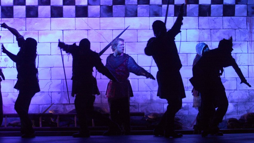 members of the Commonwealth Shakespeare Company rehearse a scene under blue stage lights from Shakespeare's Henry V in Bosto
