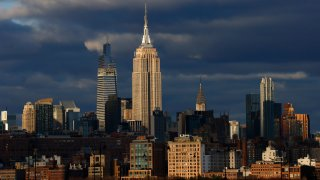 The sun sets on the skyline of midtown Manhattan, the Empire State Building, One Vanderbilt and the Chrysler Building in New York City