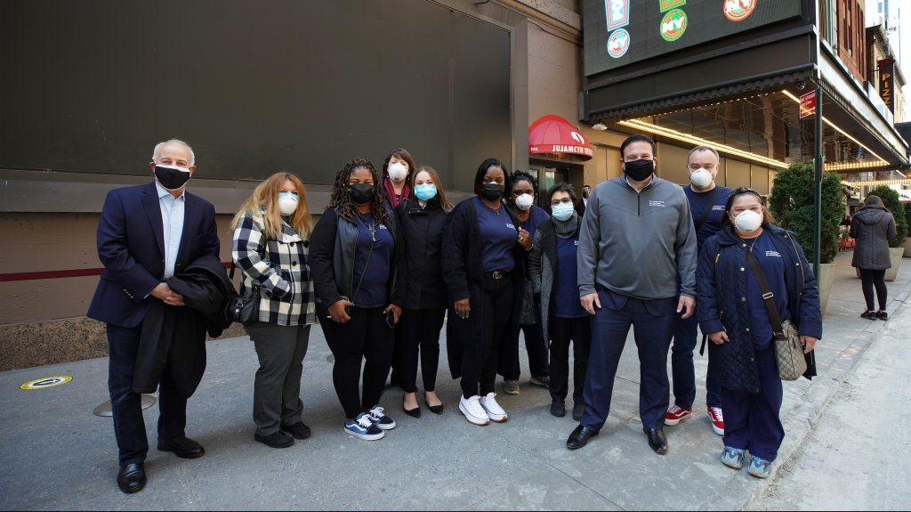 Healthcare workers and Jordan Strohl (3rd right) from The Actors Fund Home pose for a photo as Broadway's St. James Theatre reopens with an exclusive performance for frontline workers as part of NY PopsUp