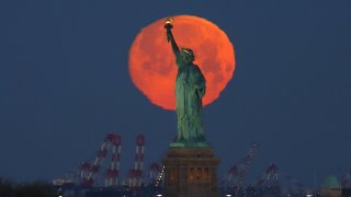 Pink supermoon behind Statue of Liberty