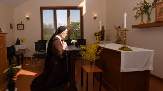 The Rev. Sister Barbara Smith, of the Order of Discalced Carmelites, prays on a prayer bench that belonged to The Rev. Mychal Judge, the Fire Department of New York's chaplain who died in the 2001 attacks on the World Trade Center, at the Episcopal Carmel of Saint Teresa in Rising Sun, Md., on Sunday, April 4, 2021. The Episcopal Carmel of Saint Teresa donated the prayer bench to the National Sept. 11 Memorial and Museum, representatives of which acquired the bench later in the morning.