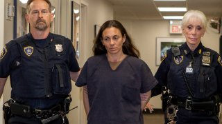 In this June 12, 2019 photo, former NYPD police officer Valerie Cincinelli, center, is escorted for an appearance in Nassau County Matrimonial Court in Mineola