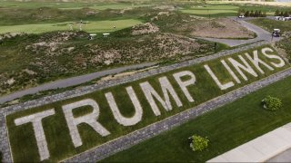 Patrons play the links as a giant branding sign is displayed with flagstones at Trump Golf Links at Ferry Point in the Bronx borough of New York on Tuesday, May 4, 2021. (AP Photo/John Minchillo)