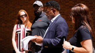 From left, Brooke Vaughn, her husband former NFL player Clarence Vaughn III, former NFL player Ken Jenkins and his wife Amy Lewis read a letter before delivering tens of thousands of petitions demanding equal treatment for everyone involved in the settlement of concussion claims against the NFL, to the federal courthouse in Philadelphia, Friday, May 14, 2021.