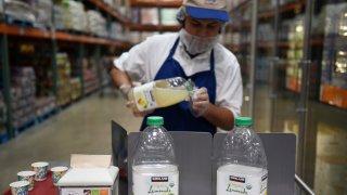 An employee fills cups with samples of Costco Wholesale Corp. Kirkland Signature brand organic lemonade