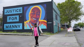 """A woman walks past a mural honoring Manuel """"Manny"""" Ellis, Thursday, May 27, 2021, in the Hilltop neighborhood of Tacoma, Wash., south of Seattle. Ellis died on March 3, 2020 after he was restrained by police officers. Earlier in the day Thursday, the Washington state attorney general filed criminal charges against three police officers in the death of Ellis, who told the Tacoma officers who were restraining him he couldn't breathe before he died."""