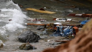 Wreckage and debris from a capsized boat wash ashore at Cabrillo National Monument near where a boat capsized just off the coast, May 2, 2021, in San Diego.