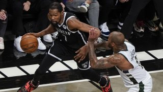 Brooklyn Nets' Kevin Durant, left, drives past Milwaukee Bucks' P.J. Tucker during the first half of Game 7 of a second-round NBA basketball playoff series