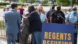 Jon Vaughn (R), former University of Michigan and former NFL football player, and Richard Goldman, a former UM student sports announcer, hug at a press conference on the University of Michigan campus on June 16, 2021 in Ann Arbor, Michigan.