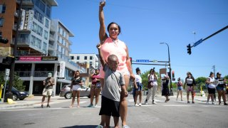 Starr Patterson stood with a child as they raised their first in the intersection of West Lake Street and Girard Friday afternoon as protesters shut down traffic near the site of the shooting death of Winston Smith in Uptown.