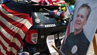 ARVADA, COLORADO - JUNE 22: Flowers, flags and notes cover a patrol car and bike outside Arvada City Hall during a memorial for Arvada Police Officer Gordon Beesley on June 22, 2021 in Arvada, Colorado. Officer Beesley was killed during a shooting in Olde Town Arvada.