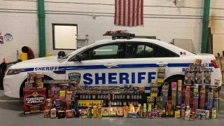 Thousands of dollars in contraband fireworks sit next to a sheriff's vehicle.