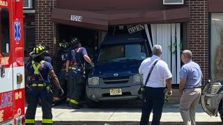 Firefighters inspect a driving school in Asbury Park where a driver backed into the front of the business.