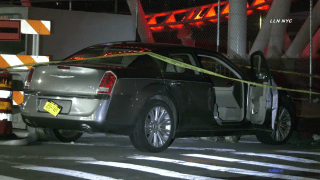 Police tape surrounds a dark sedan crashed in Coney Island following a carjacking, police said.