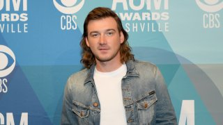 Morgan Wallen stands in a white shirt and jean jacket.