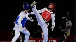 South Korea's Lee Daehoon (Blue) and Uzbekistan's Ulugbek Rashitov (Red) compete in the taekwondo men's -68kg elimination round bout during the Tokyo 2020 Olympic Games at the Makuhari Messe Hall in Tokyo on July 25, 2021.