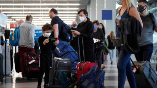 FILE - Travelers line up at O'Hare airport in Chicago, July 2, 2021.