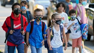 In this Tuesday, Aug. 10, 2021 file photo, Students, some wearing protective masks, arrive for the first day of school