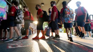 Wearing masks to prevent the spread of COVID-19, elementary school students line up to enter school for the first day of classes in Richardson, Texas, Tuesday, Aug. 17, 2021. Despite Texas Gov Greg Abbott's executive order banning mask mandates by local officials, the Richardson Independent School District and many others across the state are requiring masks for students.