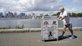 Paul Veneto pushes a beverage cart along the Boston harbor, Saturday, Aug. 21, 2021