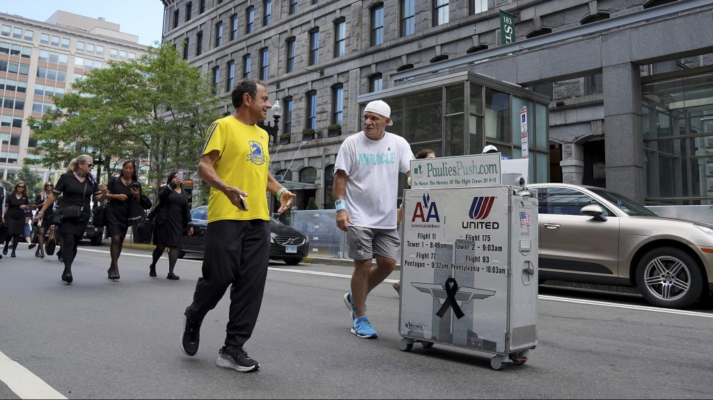 Paul Veneto, right, is joined by Boston Marathon Race Director Dave McGillivray, front left, as Veneto pushes a beverage cart along State Street, in Boston