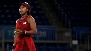 Naomi Osaka holds a tennis ball as she prepares to serve.