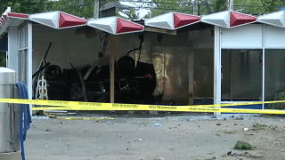A car lays on its side after crashing into Robo Automatic Car Wash in East Patchogue.