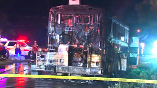 Police tape cordons off a burnt bus after crews extinguished a fire.