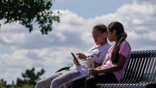 Savannah Brown and Glendy Stollberg use their phone in Kilbourn Reservoir Park