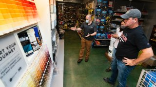 Billy Wommack, purchasing director at the W.S. Jenks & Sons hardware, left, works with customer Tim Wood, right, picking a paint color