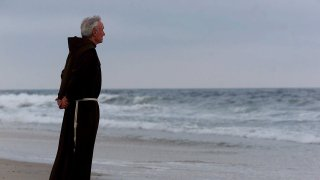 In this July 17, 2000, file photo, the Rev. Mychal Judge, the Fire Department of New York's chaplain with the New York City Fire Department, stands at the shore before a service to remember the 230 people who died on July 17