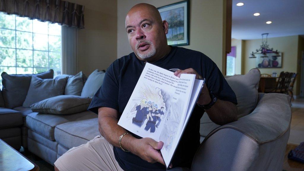 "Will Jimeno holds the children's book he wrote, ""Immigrant, American, Survivor."""