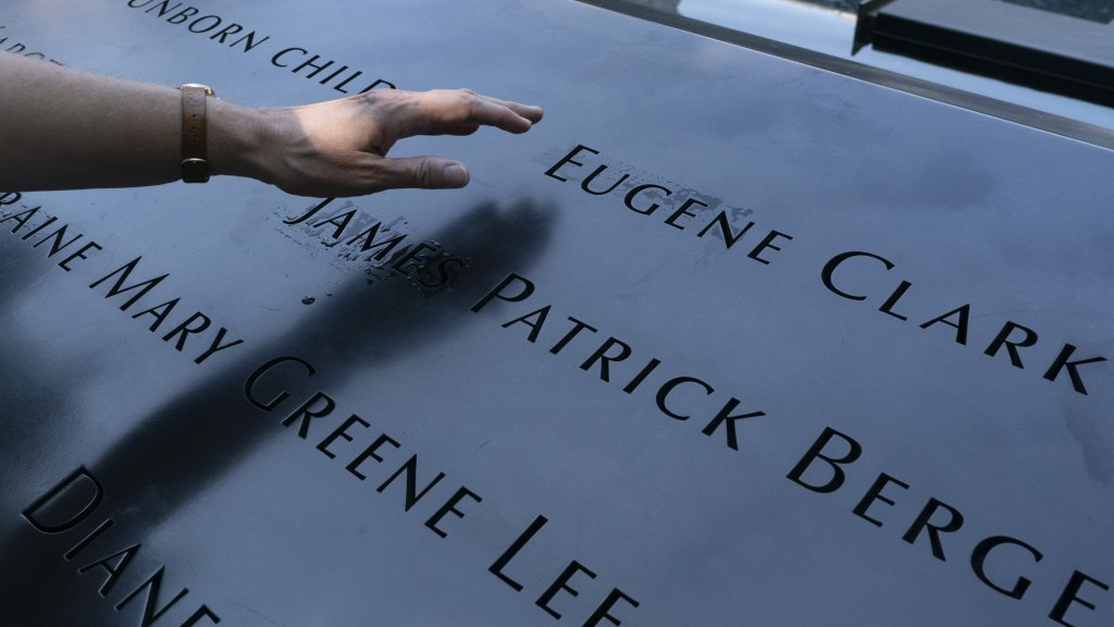 ésirée Bouchat reaches towards the inscribed name of James Patrick Berger at the National September 11 Memorial