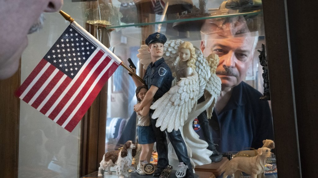 Retired NYPD Officer Mark DeMarco, is seen in a reflection off a display cabinet where he keeps memorabilia from 9/11